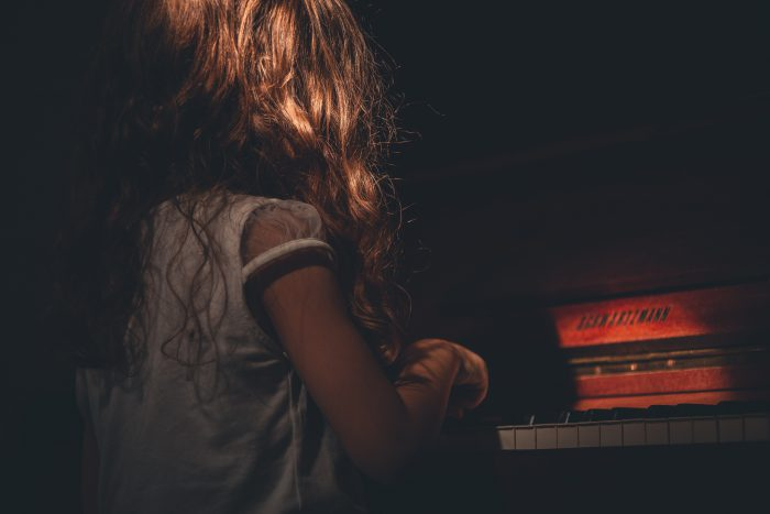 child playing piano keys