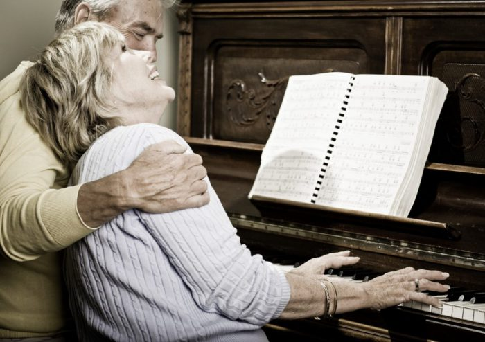 older couple at piano laughing