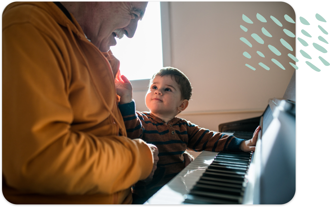 Senior man with young child sitting at the piano together