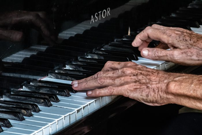 older person playing piano