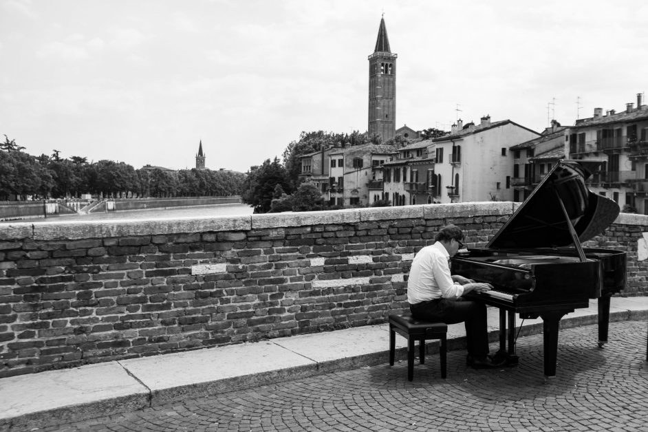 man playing grand piano on stone bridge over river