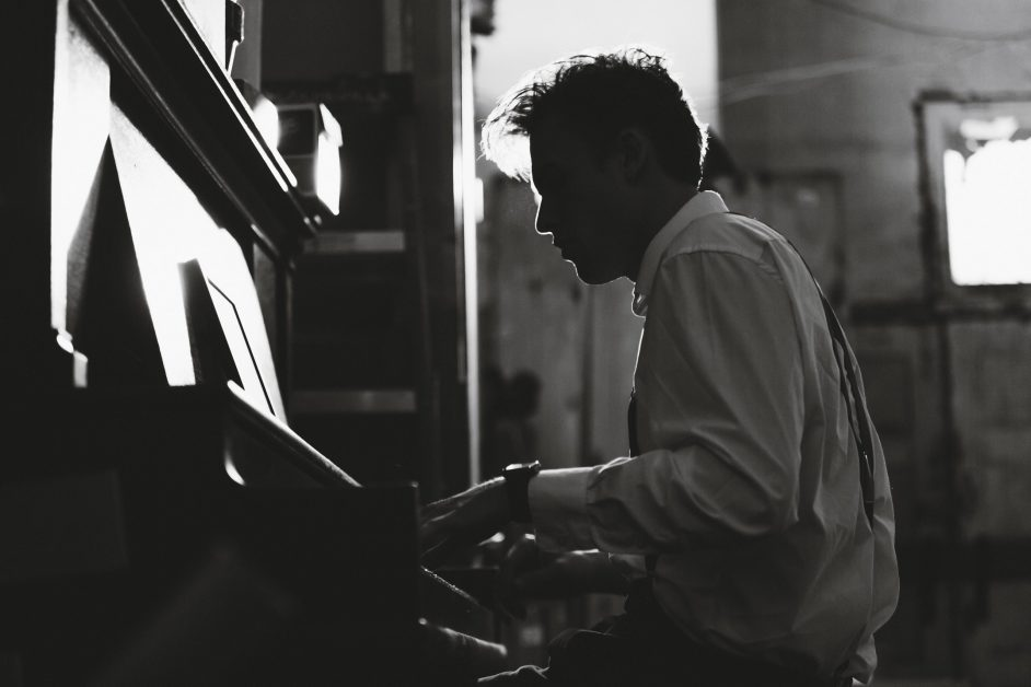 younger man playing upright piano