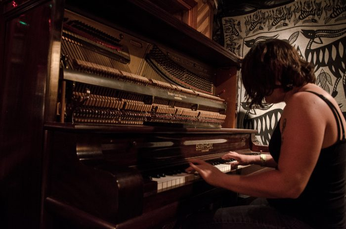 woman in black tank top playing the piano